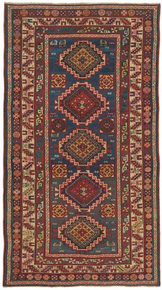 Caucasian Kazak, 4ft 4in x 7ft 10in, Late 19th Century. A spectacularly animated, brilliantly abrashed field transitions through stunning hues of teal, royal, cobalt and azure blues in this compelling 19th century Caucasian Kazak rug. Upon this skillfully variegated background, five richly colored latch hook medallions ascend the narrow field, alternating between gold and crimson. Charming gazelle forms appear throughout the field adding the individuality that is much desired in tribal rugs.