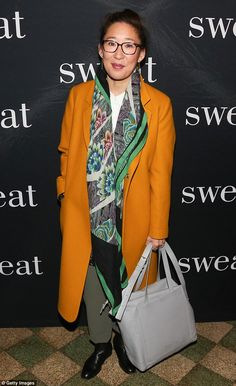 Mix and match: Grey's Anatomy star Sandra Oh, 45, came to the opening in a gold overcoat with khaki pants and black shoes. She added a colorful silk scarf and black-rimmed spectacles