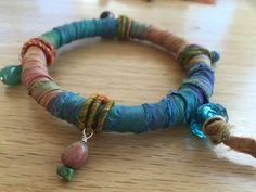 Bangle bracelet made with repurposed turquoise blue and copper colored sari silk ribbon