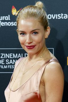 Who: Sienna Miller What: Modern Ballerina How-To: A tight top knot becomes instantly more forgiving when you take the part (especially a middle part) out of the equation, and brushing the hair back with hairspray over gel or serum gives a sleek finish without any wetness.  Editor's Pick: Guerlain KissKiss Creamy Satin Finish Lipstick in Red Insolence, $37, sephora.com.   - HarpersBAZAAR.com