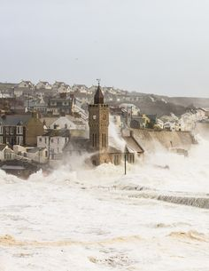 High tides, big storms, Porthleven, Cornwall, massive waves flooded over the sea defences. Waves washing over the iconic clocktower. England And Scotland, England Uk, London England, Oxford England, Yorkshire England, Yorkshire Dales, British Isles, British Seaside, English Countryside