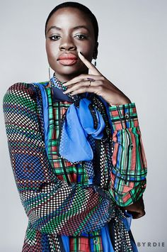 Danai Gurira models a multi-colored plaid blouse with scarf tie in a new beauty editorial. (via @byrdiebeauty)
