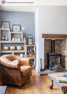 Sielski salon z kozą. Wnęka na piec wyłożona cegłą. Piękny drewniany stolik kawowy na kółkach.