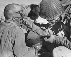 American medic helping wounded half track gunner swallow a sulfa tablet before treating his wounds during the battle for control of Sened area.