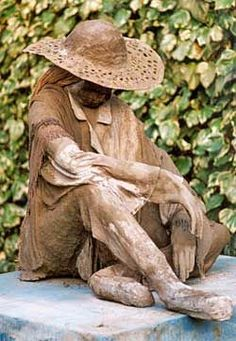 """Gartenskulptur aus einem Gerüßt gemacht aus Zeitungsrollen,""""angezogen"""" mit Atlkleidern in Zement getaucht. Figure with sun hat. Front view"""