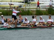 312b The picture is focusing on the entire rowing team instead of zooming in on the one celebrating. It shows them in a positive light because they are all celebrating and waving. The photographer tried to include as little of the empty stands as possible to make it look like a more popular sport. Also, the uniforms can be seen clearly to emphasize that they are German.