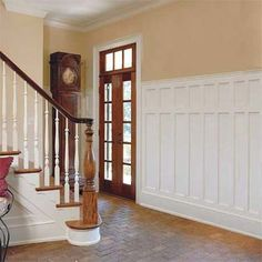 Double-panel wainscoting: Two-tier wainscoting mirrors the look of the French doors topped with a divided-light transom. | Photo: Jean Allsopp