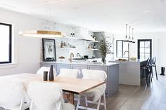 Open plan dining-kitchen space with light gray hues, gold and brass accents, and wood floors