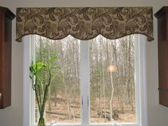 Shaped cornice design over sink window. Fabric pattern complements cabinets and colors in kitchen.