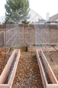 trellis with garden boxes near stone wall