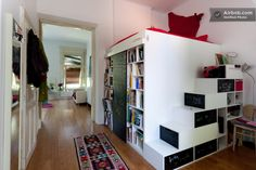 Cool bookshelves that double as steps to the lofted bed in a colorful studio in Budapest.- Can I have this now??????