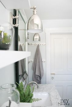 Amazing bathroom features pale gray walls framing Pottery Barn Bevel Mirror flanked by Hudson Valley Lighting Monroe Wall Sconce over carrera marble top vanity paired with Virtu USA PS-1201 Talia Faucet in Brushed Nickel next to stacked floating shelves installed over toilet.