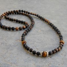 Beautiful piece, with 108 beads, made with genuine tiger ebony wood (for strength) beads, an African trade bead in between each bead, and tiger's eye gemstones (for prosperity) on the 7th bead of each