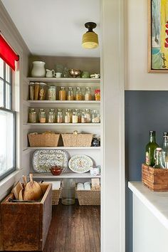 Open pantry shelves keep supplies handy just off the kitchen.  Farmhouse Organizing