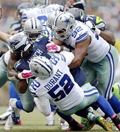 Dallas Cowboys defensive end Jack Crawford (58) and defensive end Jeremy Mincey (92) tackle Seattle Seahawks running back Marshawn Lynch during the second half of Dallas' 30-23 win Sunday, October 12, 2014 at CenturyLink Field in Seattle, Wash. (G.J. McCarthy/The Dallas Morning News)