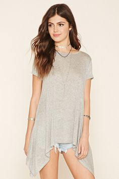 A burnout knit top featuring a longline trapeze silhouette, short sleeves, and a round neckline.