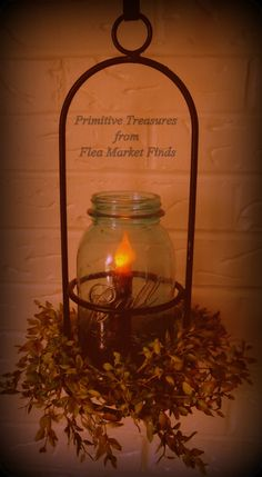 early lighting..found the black wrought iron candle holder and jar at the thrift store. Added a grungy battery candle and some greens. Prim decor on the cheap!!