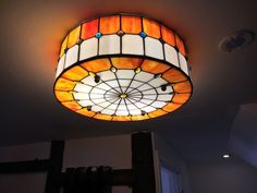 A Beautiful Tiffany Style Flush Mounted Ceiling Light Featuring Orange And Cream Glass Panels