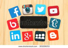 KIEV, UKRAINE - JULY 01, 2015: Famous social media icons such as: Facebook, Twitter, Blogger, Linkedin, Tumblr, Myspace and others, printed on paper and placed around iPhone on wooden background.
