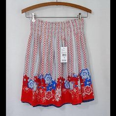 """CAbi Happy Day Floral short reversible skirt This adorable skirt is reversible, giving you two looks in one skirt!  Smocked elastic waist. 100% rayon.  Waist 12"""" across. Length 18.5"""". Brand new with tag. Smoke free and pet free home. CAbi Skirts"""