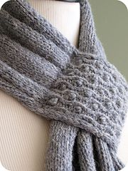 """A lush and elegant scarf showcasing a simple twisted stitch cable and bobble design. The sides are finished with an i-cord that is knit while you work the scarf, the bottom with a simple looped edging. Knitted pleats gather the scarf from 12"""" wide to 4"""" wide, where a small cabled panel is folded to create a loop through which you pull your scarf end. Knit in Rowan Lima, this scarf is light, yet lofty and oh so cozy."""