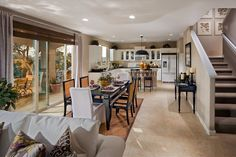 A stylish dining area and kitchen open to an inviting outdoor space. The Hunter plan, a new home by McCaffrey Homes at The Gallery In Clovis. Clovis, CA.