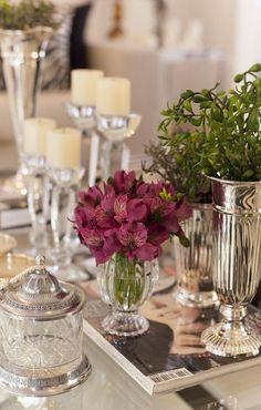 A delicadeza das flores e das velas harmoniza com a elegância do metal das peças vintage