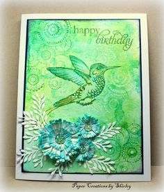 The background started with Distress Inks (Citron, Mowed Lawn and Peacock) on my craft mat, spritzing water and then dragging mixed paper through. After drying with a heat gun I stamped Circle Clusters with water. When the background was dry again I over stamped with Mowed Lawn Distress Ink using Circle Clusters and highlighted with a white gel pen. The beautiful Booted-Racket tail Hummingbird was stamped with Memento Ink, colored with Distress Inks using a brush and water on my craft mat…