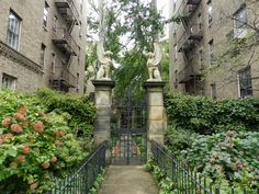 """Jackson Heights, Queens is believed to be the site of the first garden city community in the United States. These """"gardens"""" or private parks are found within the numerous garden-style apartment buildings in the neighborhood and can only be accessed by residents, though some are visible to the public. A peak into the garden at The Towers. Photo via Mike's Historic Buildings."""