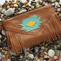 """PLEASE note this item has a 4 to 5 week production time.  //FEATURES//  • caramel leather with hand cut tribal design and fringe on the front • antique metal zipper • caramel leather wrist strap included • natural canvas lining • NO inside pockets  measures approx 10"""" x 6"""""""