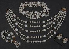 MIRIAM HASKELL DEMI PARURE: White glass beads in oval and round shapes with crystal and rhinestone rondelles, graduated five strand necklace, long necklace, double strand bracelet and matching ear clips. Signed.