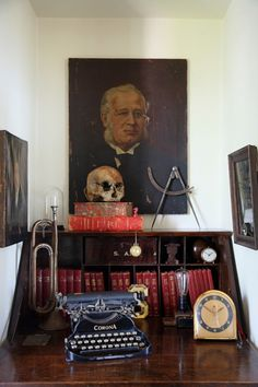 The small quarter-sawn oak secreter. an ever-changing vignette. vintage oil portraits mingle with a science book series .The 1907 Corona typewriter. A human skull as Memento Mori in this tableau is part of a Victorian-era medical collection.
