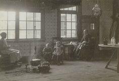Interieur te Lonneker.  Twee vrouwen en twee kinderen zitten bij het open vuur. Ze zijn gekleed in Twentse streekdracht #Overijssel #Twente #Saksen
