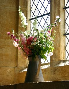 Vintage jug of flowers as a window dressing for the church. Strictly seasonal British eco wedding flowers by Common Farm in Somerset.