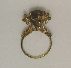 14th century. Gold ring, the pyramidal bezel nielloed with a flower on each…