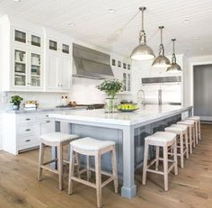 White and grey kitchen with wooden floor and large island