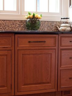 Beautiful cherry cabinets with dark counters, tiles tie it all together