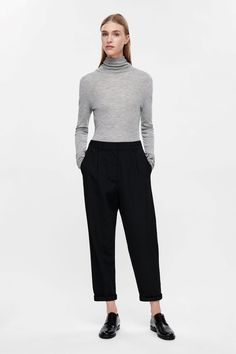 This knitted roll-neck top is made from extra-fine wool with a sheer, lightly ribbed texture. A comfortable close fit, it has long sleeves and a raw-edge curved hem. Wear it on its own or as an extra lightweight layer.