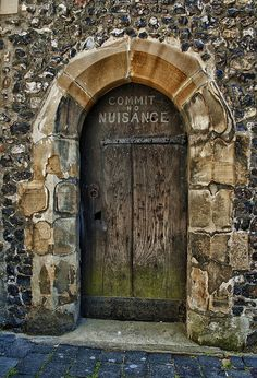 """Commit No Nuisance"". Clock tower entrance door.  St Albans School,  an independent school in St Albans, Hertfordshire, founded in 948 AD."