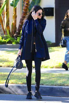 Kendall Jenner con brigo azul marino, leggings negros, zapatillas azul marino, bolso de cuero con tachuelas, de Alexander Wang y gafas de sol, de Ahlem Eyewear.