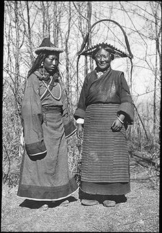 Photographer: Lt. ColR. S. Kennedy? Willoughby, Patrick Rosemeyer?, Collection: Sir Charles Bell, Date of Photo: 1920-1921 or 1922, Region: Lhasa .  A Golok woman (left) and a Tsang woman (right) in park in Lhasa.  Bell describes them as being 'two friends'.  Both wear regional headdresses, coats, aprons and clothing, amulet boxes, and accessories.