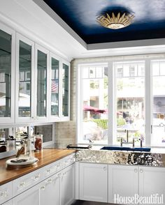 Mick De Giulio's  2012 Kitchen of the Year  --- butler pantry.  Ceiling is painted Glidden's Sotf Sapphire,  Apollo light fixture by Suzanne Kasletl, walnut and  hammered stainlett'steel countertops