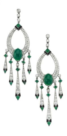 A PAIR OF ART DECO EMERALD AND DIAMOND EAR PENDANTS, CIRCA 1928. Each designed as a circular-cut diamond tapered openwork oval, set with an oval cabochon emerald, to the collet diamond and bezel-set emerald drops suspending a tapered diamond-set fringe with onyx and emerald geometric motif terminals, 2 3/4 ins., mounted in platinum.