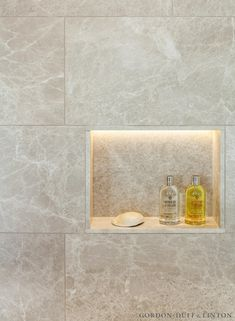 Natural stone marble tiles in bathroom. Shower niche with LED lighting detail.