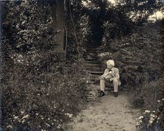 Samuel Clemens seated on the steps leading up to his study at Quarry Farm, East Hill, Elmira, New York. July 17, 1903