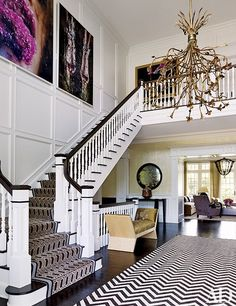 A vintage chandelier from Historical Materialist hangs in the entrance hall; the two large photographs are by Marilyn Minter, and the stair runner is by Patterson Flynn Martin.