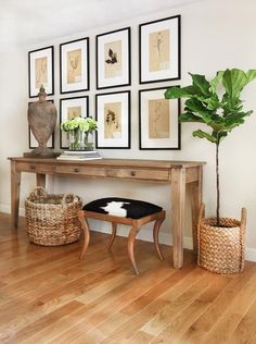Chic foyer features a seagrass basket and a cowhide stool tucked under a…