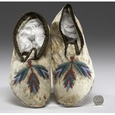 Santee Sioux Beaded Hide Moccasins thread and sinew-sewn with beadwork in colors of red white-heart, greasy green, translucent plum, and light blue; cuffs edged in khaki sateen, length 10.5 in. late 19th century Price Realized Including Buyer's Premium $180 08/11/2016