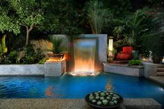 Delightful backyard escape with pool, waterfalls and ample greenery [Design: Estate Pools & Landscapes Design/Build]