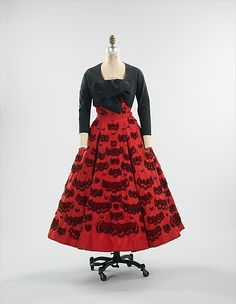 DIOR Evening ensemble 1952. Christian Dior made masterful use of surface embellishments for his evening dresses of the early 1950s. In this example from 1952, Dior's characteristic attention to detail shows in the refined placement and graduation of the embroidery and appliqué elements. The pairing of black and red shows a Spanish influence, with the placement of the trimmings referencing the tiers of a flamenco skirt.